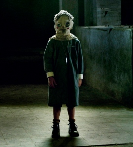 "Masked children wander through the corridors of ""The Orphanage."""